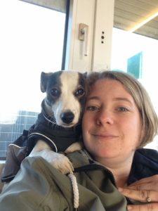 hundebesitzerin mit ihrem hund auf der schulter
