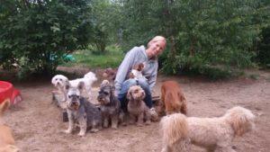 hundebetreuerin von dogs place im freien umringt von vielen hunden
